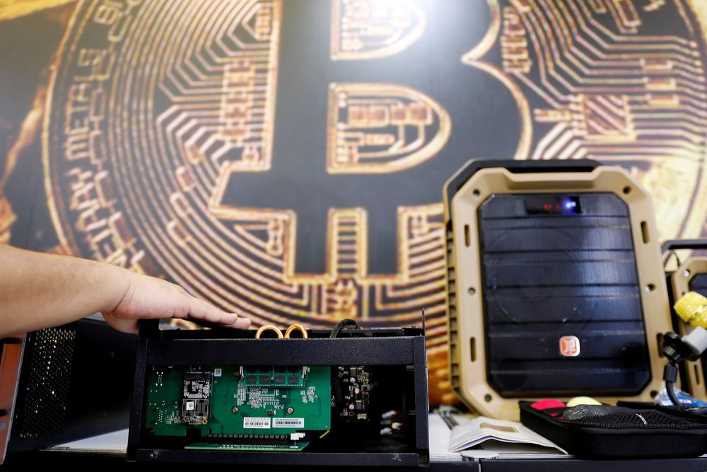A cryptocurrency mining computer is seen in front of bitcoin logo during the annual Computex computer exhibition in Taipei, Taiwan, June 5, 2018. — Reuters pic