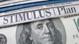 The words stimulus plan on paper atop U.S. currency