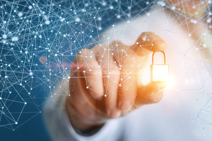 A person holding a golden glowing lock that's surrounded by a latticework representing blockchain.